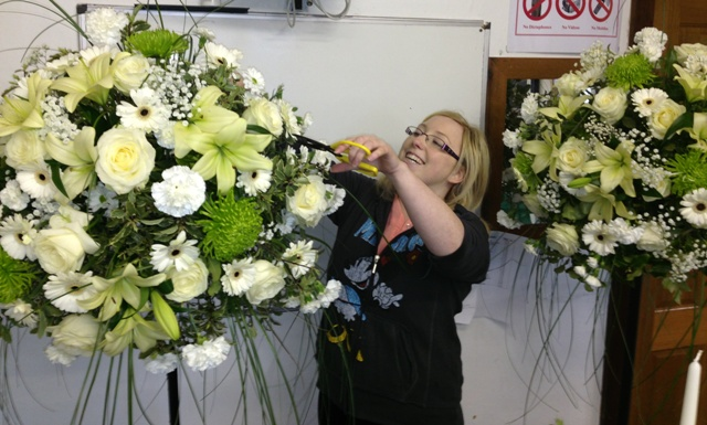 Girl making white topiary balls from flowers at kays school of floristry