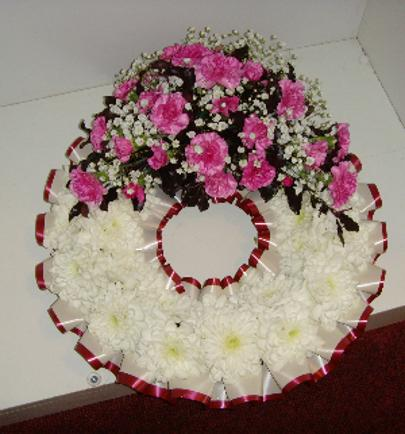 Funeral based wreath with a spray of pink flowers