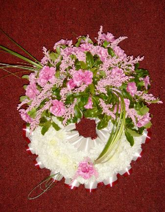 Whte round wreath with a spray of pink flowers