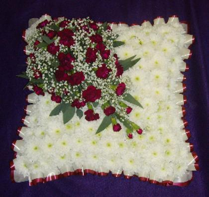 funeral cushion with a spray of red roses